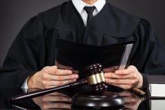 Файл удерживания судьи с мушкелом на столе стоковые изображения rf