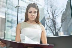 Файл чтения коммерсантки в офисе Стоковые Изображения RF