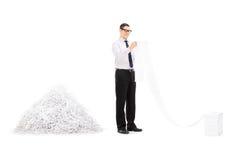 Файл чтения человека перед кучей shredded бумаги Стоковая Фотография
