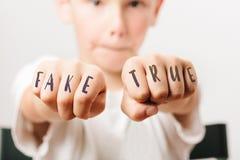 Фальшивка и истинное на кулаках школьника стоковое изображение rf