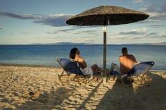 Фантазия секретов пар Пара в курорте влюбленности на море сидит на loungers под зонтиком на пляже песка Пары на каникуле Стоковые Изображения RF