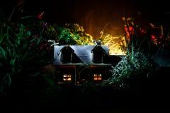 Фантазия украсила фото Малый красивый дом в траве с светом Старый дом в лесе на ноче с луной Селективный фокус стоковая фотография
