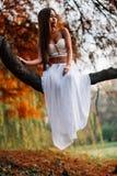 Фантастическая молодая женщина красивая фея девушки фантазии с белым длинным платьем в ветреном парке осени Стоковая Фотография