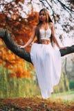 Фантастическая молодая женщина красивая фея девушки фантазии с белым длинным платьем в ветреном парке осени Стоковое фото RF