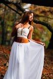 Фантастическая молодая женщина красивая фея девушки фантазии с белым длинным платьем в ветреном парке осени Стоковое Изображение RF
