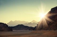 Фантастический ландшафт с горами на заходе солнца Стоковая Фотография