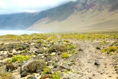 Фантастичный заколдованный ландшафт на острове Лансароте с каменной и зеленой желтой вегетацией с Атлантическим океаном и туманно стоковое изображение
