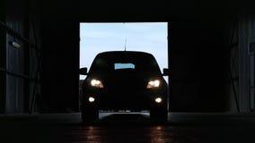 Фара автомобиля включенная большое вид спереди машины силуэта гаража видеоматериал