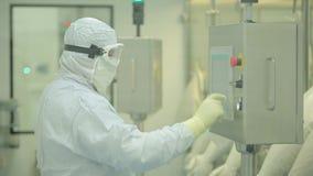 Фармацевтическая промышленность Мужское заводской рабочий проверяя качество пилюлек упаковывая в фармацевтической фабрике автомат видеоматериал