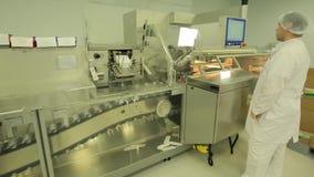 Фармацевтическая промышленность Мужское заводской рабочий проверяя качество пилюлек упаковывая в фармацевтической фабрике автомат акции видеоматериалы
