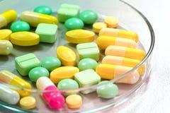 Фармацевтические пилюльки медицины в чашка Петри на таблице Стоковое фото RF