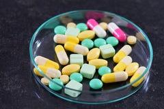 Фармацевтические пилюльки медицины в чашка Петри на таблице Стоковые Фотографии RF