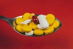 Фармацевтические таблетки медицины, на ложке против красной предпосылки стоковое изображение rf
