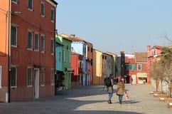 Фасады красочных зданий и туристов идя в город Burano, Италии стоковые фото