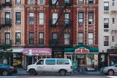 Фасады типичного блока квартир с пожарными лестницами в Манхэттене, Нью-Йорке, США стоковое изображение
