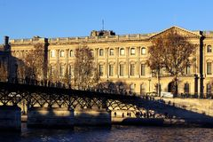 Фасад и Pont des Arts Лувра взгляда Рекы Сена окружающие стоковое изображение