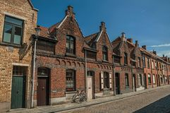 Фасад кирпича домов в типичном стиле и велосипеде Flanders's, в улице Брюгге Стоковое фото RF