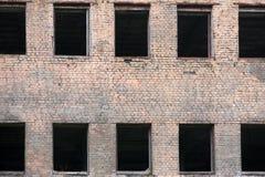 Фасад кирпича покинутого старого здания с окнами Стоковая Фотография