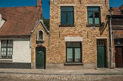 Фасад кирпича старых домов и дверей с голубым небом, в пустой улице Брюгге Стоковая Фотография RF