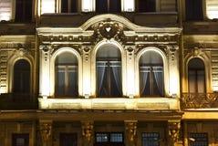 Фасад Санкт-Петербурга исторического здания в стиле барокко, балкона с Windows, освещением ночи стоковое фото
