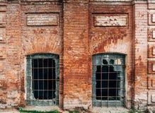 Фасад старого дома красного кирпича с сломленным стеклом Стоковое фото RF