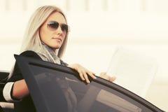 Фасонируйте бизнес-леди в солнечных очках вне ее автомобиля стоковая фотография