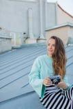 Фасонируйте взгляд, довольно холодную модель молодой женщины с ретро камерой фильма вьющиеся волосы outdoors Стильный фотограф де Стоковые Фотографии RF