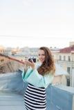 Фасонируйте взгляд, довольно холодную модель молодой женщины с ретро камерой фильма вьющиеся волосы outdoors Стильный фотограф де Стоковое Изображение RF