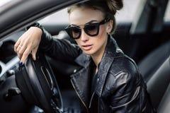 Фасонируйте внешнее фото сексуальной красивой женщины с темными волосами в черной кожаной куртке и солнечных очках представляя в  Стоковое Изображение RF