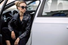 Фасонируйте внешнее фото сексуальной красивой женщины с темными волосами в черной кожаной куртке и солнечных очках представляя в  Стоковые Фото