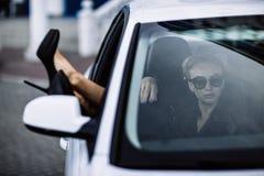 Фасонируйте внешнее фото сексуальной красивой женщины с темными волосами в черной кожаной куртке и солнечных очках представляя в  Стоковое Фото