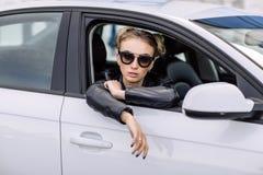 Фасонируйте внешнее фото сексуальной красивой женщины с темными волосами в черной кожаной куртке и солнечных очках представляя в  Стоковая Фотография