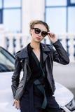 Фасонируйте внешнее фото сексуальной красивой женщины с темными волосами в черной кожаной куртке и солнечных очках представляя в  Стоковое фото RF