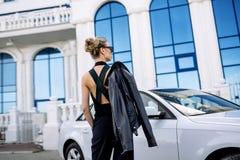 Фасонируйте внешнее фото сексуальной красивой женщины с темными волосами в черной кожаной куртке и солнечных очках представляя в  Стоковая Фотография RF