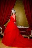 Фасонируйте всход красивой белокурой женщины в длинном красном платье на винтажной красной предпосылке софы Стоковое Изображение