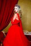 Фасонируйте всход красивой белокурой женщины в длинном красном платье на винтажной красной предпосылке софы Стоковое Изображение RF