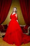 Фасонируйте всход красивой белокурой женщины в длинном красном платье на винтажной красной предпосылке софы Стоковое Фото