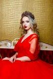Фасонируйте всход красивой белокурой женщины в длинном красном платье на винтажной красной предпосылке софы Стоковые Фото