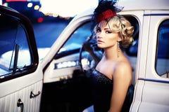 Фасонируйте девушку в ретро стиле представляя в старом автомобиле Стоковое фото RF