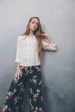 Фасонируйте девушку подростка стоя против голубой текстурированной предпосылки стены grunge стоковые фото