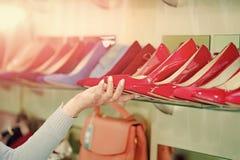 Фасонируйте женский ботинок от красной и голубой кожи в руке Стоковая Фотография RF