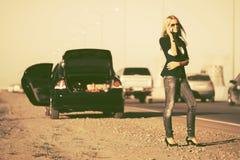 Фасонируйте женщину вызывая на сотовом телефоне рядом с сломленным автомобилем стоковые изображения