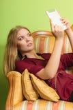 Фасонируйте женщину кладя на софу с таблеткой ПК Стоковая Фотография RF