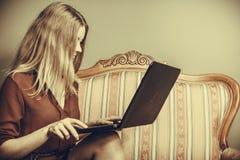 Фасонируйте женщину сидя на софе используя компьтер-книжку ПК Стоковые Изображения
