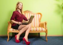 Фасонируйте женщину сидя на софе используя компьтер-книжку ПК Стоковое Изображение RF