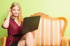 Фасонируйте женщину сидя на софе используя компьтер-книжку ПК Стоковые Фотографии RF