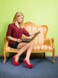 Фасонируйте женщину сидя на софе используя компьтер-книжку ПК Стоковые Фото