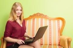 Фасонируйте женщину сидя на софе используя компьтер-книжку ПК Стоковая Фотография