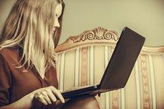 Фасонируйте женщину сидя на софе используя компьтер-книжку ПК Стоковая Фотография RF