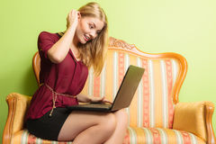 Фасонируйте женщину сидя на софе используя компьтер-книжку ПК Стоковое Фото